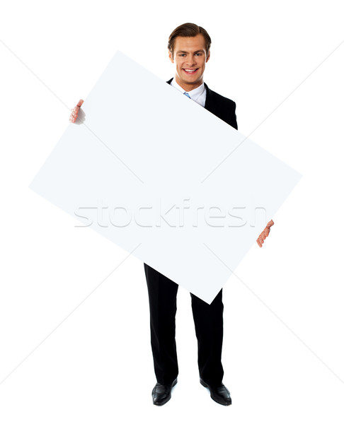 Young corporate male holding tilted blank billboard Stock photo © stockyimages