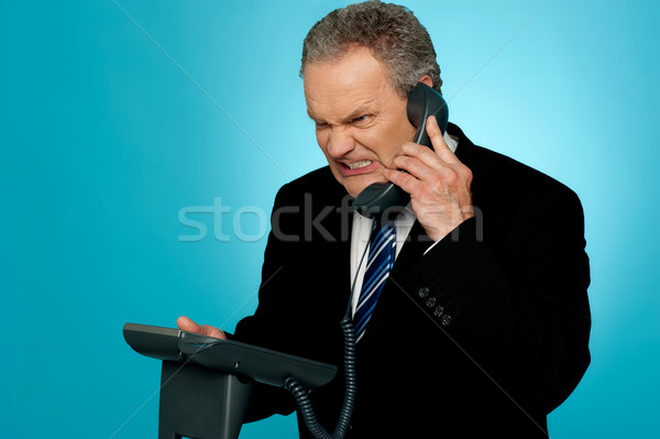 Irritated businessman communicating on phone Stock photo © stockyimages