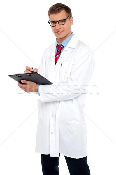 Guapo médico escrito prescripción mirando hombre Foto stock © stockyimages