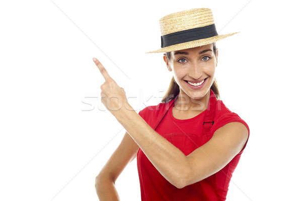 Smiling woman wearing straw bowler hat pointing away Stock photo © stockyimages