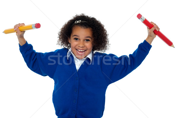 Fun loving elementary girl dancing with pencils in both her hands Stock photo © stockyimages