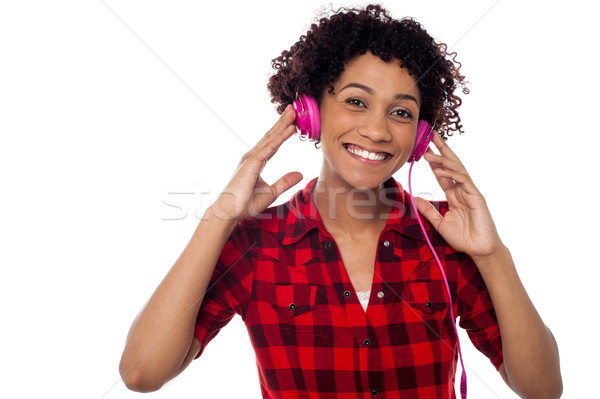 Smiling woman with pink headphones on Stock photo © stockyimages