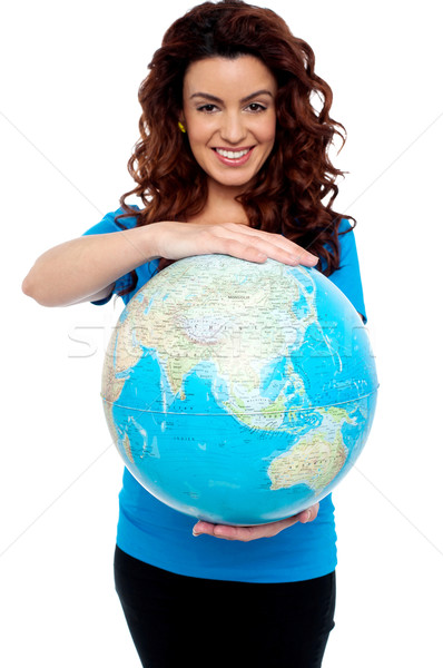 Cheerful girl holding globe safely with both hands Stock photo © stockyimages