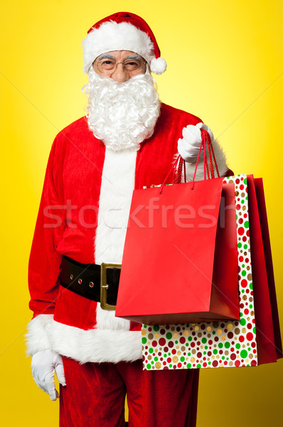Joyous Santa posing with colorful shopping bags Stock photo © stockyimages