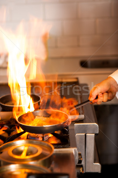 Chef cooking in kitchen stove Stock photo © stockyimages