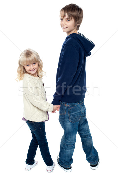 Delightful kids turning back and facing camera Stock photo © stockyimages