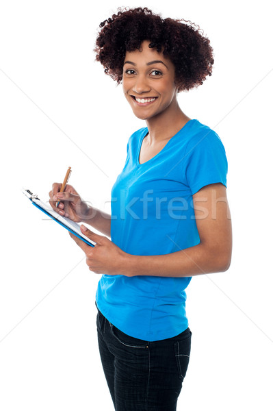 Young lady documenting instructions on clipboard Stock photo © stockyimages