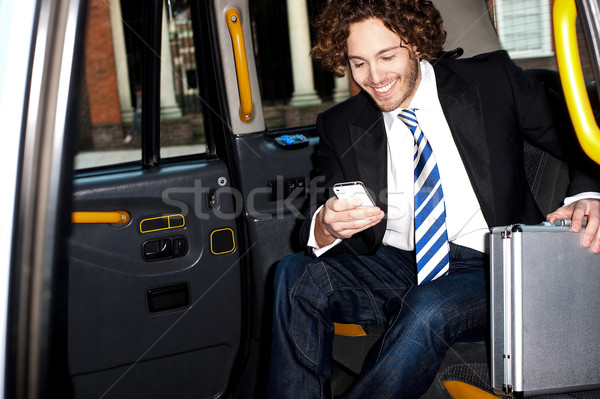 Man messaging through cellphone inside taxi cab Stock photo © stockyimages