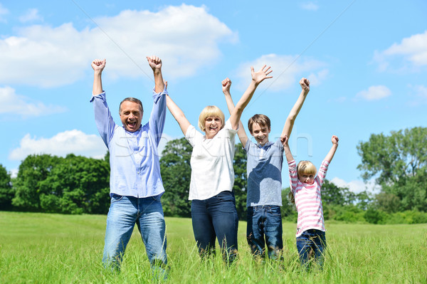Happy family together raising their arms Stock photo © stockyimages