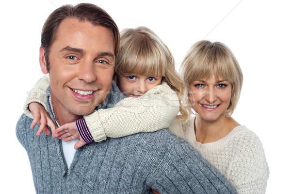 Fun loving family of three, girl piggybacking her father. Stock photo © stockyimages