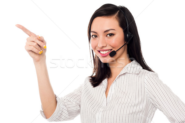 Asian call center executive pointing away Stock photo © stockyimages