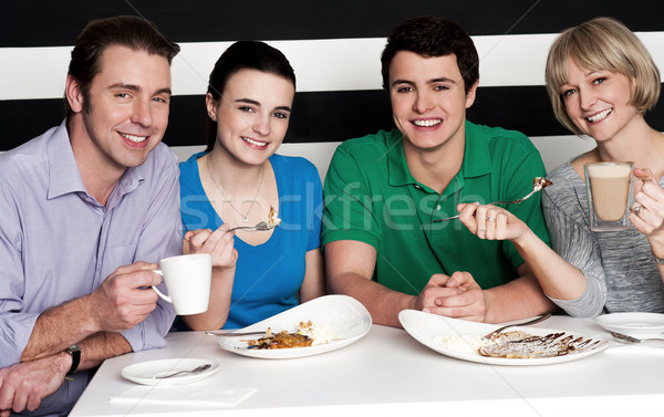 Happy family of four at restaurant Stock photo © stockyimages