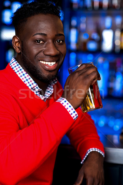 African guy drinking chilled beer Stock photo © stockyimages