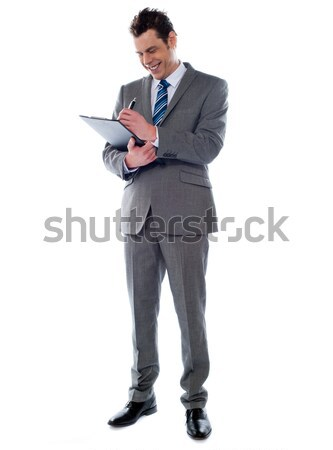 Successful businessman writing notes on clipboard Stock photo © stockyimages