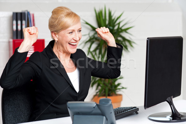 Excited corporate lady looking at computer screen Stock photo © stockyimages