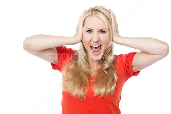 Screaming young woman holding her head Stock photo © stockyimages