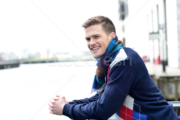Handsome man leaning on railing at river Stock photo © stockyimages