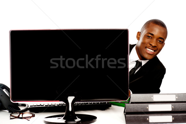 Businessman peeping from behind lcd monitor Stock photo © stockyimages