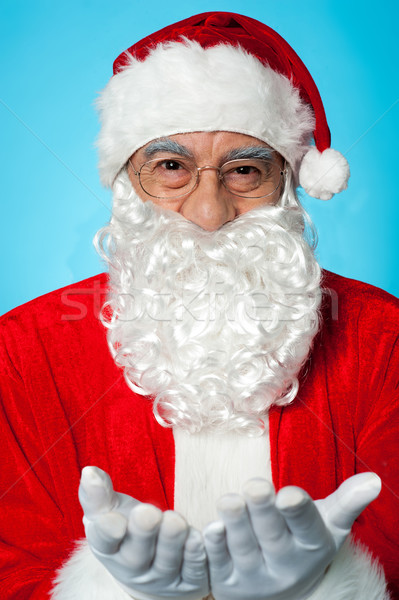 Smiling aged Santa posing with open palms Stock photo © stockyimages