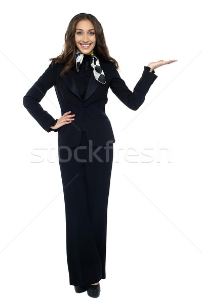 Pretty air hostess presenting copy space with open palm Stock photo © stockyimages