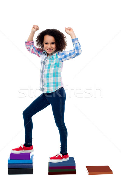 Active girl kid climbing on notebooks Stock photo © stockyimages