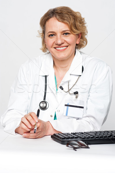 Confident female surgeon sitting idle, holding pen Stock photo © stockyimages