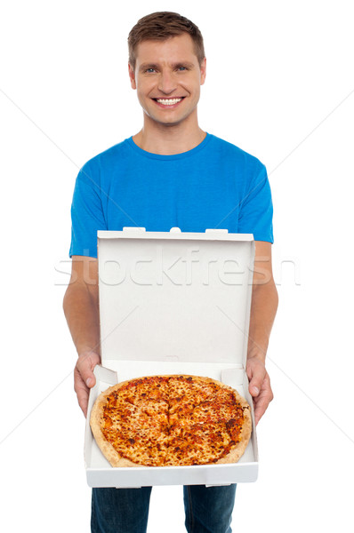 Smiling man offering pizza to you Stock photo © stockyimages