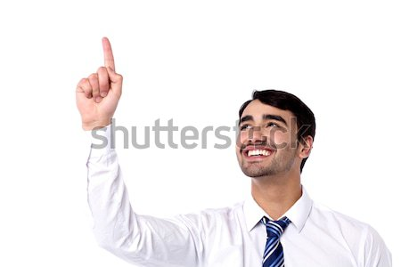 Cheerful male executive pointing upwards Stock photo © stockyimages