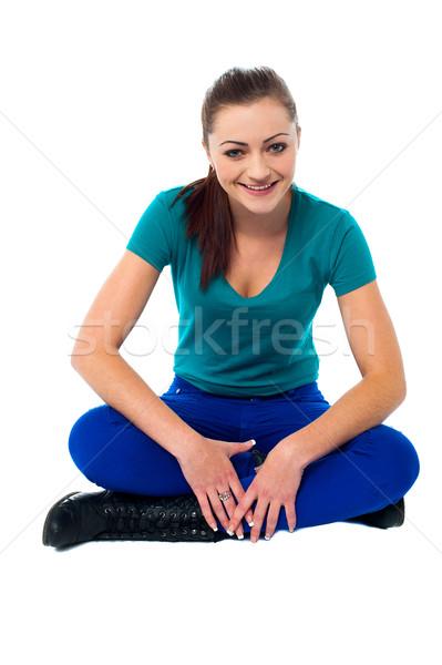 Trendy girl in casuals relaxing on studio floor Stock photo © stockyimages