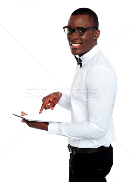 Smiling african operating touch-pad device Stock photo © stockyimages