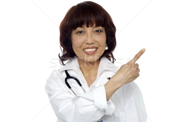 Matured surgeon pointing at the copy space Stock photo © stockyimages