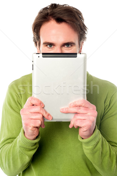 Man hiding his face with tablet device Stock photo © stockyimages