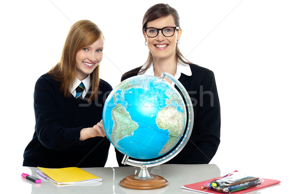 Teacher and student viewing globe in geography classroom Stock photo © stockyimages