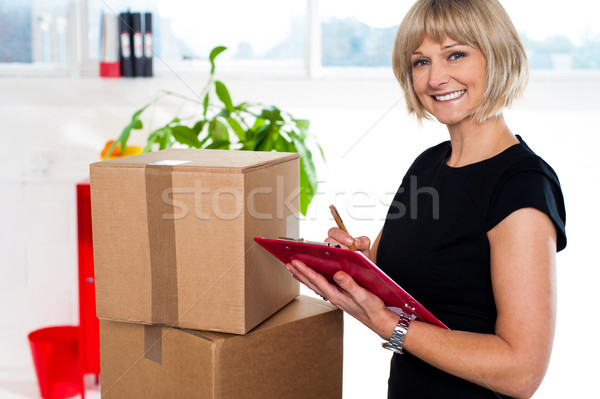 Casual woman documenting list of goods on clipboard Stock photo © stockyimages