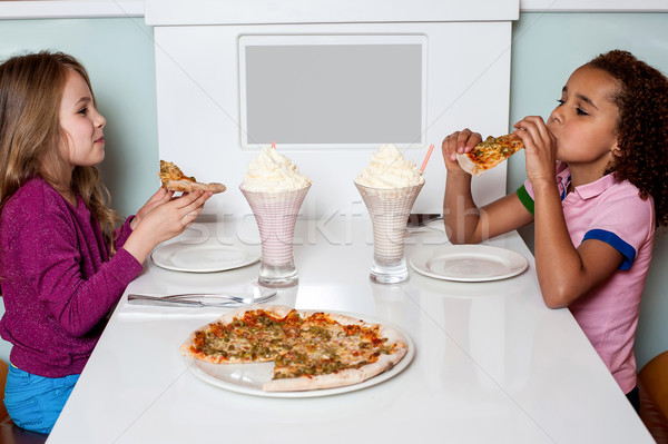 Little girls enjoying pizza in a restaurant Stock photo © stockyimages