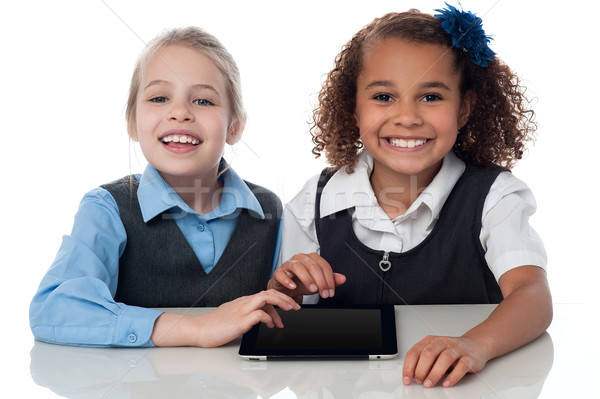 Smiling school girls playing on touchpad Stock photo © stockyimages