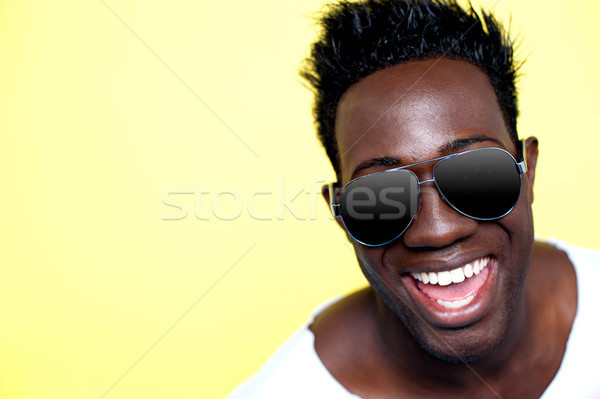 Closeup of joyful young african guy in sunglasses Stock photo © stockyimages