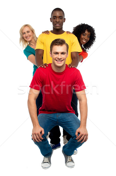 Young people standing behind semi seated guy Stock photo © stockyimages
