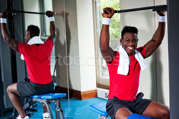 Confident young african guy working out in gym Stock photo © stockyimages