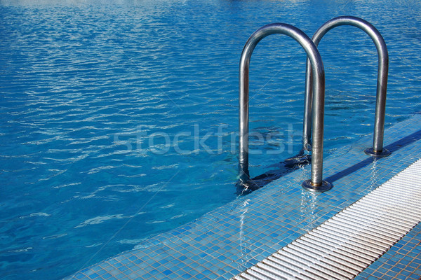 Swimming pool with steel ladder Stock photo © stockyimages
