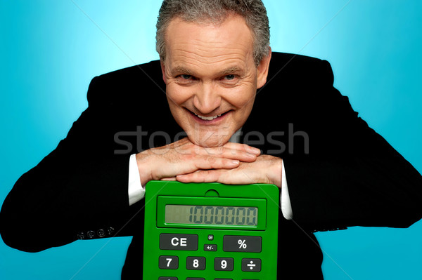 Aged corporate male resting face on big calculator Stock photo © stockyimages