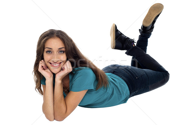 Elegant female with cheeky expression relaxing on the floor Stock photo © stockyimages