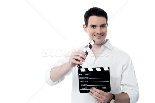 Smiling man holding a movie clap isolated on white Stock photo © stockyimages
