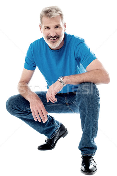 Handsome man crouching down and smiling Stock photo © stockyimages