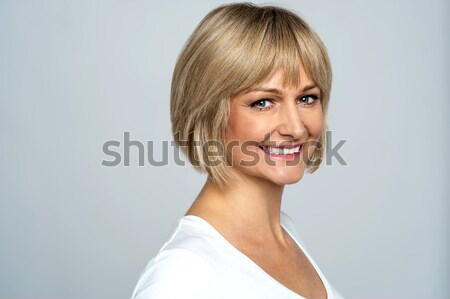 Snap shot of a cheerful blonde, side pose Stock photo © stockyimages