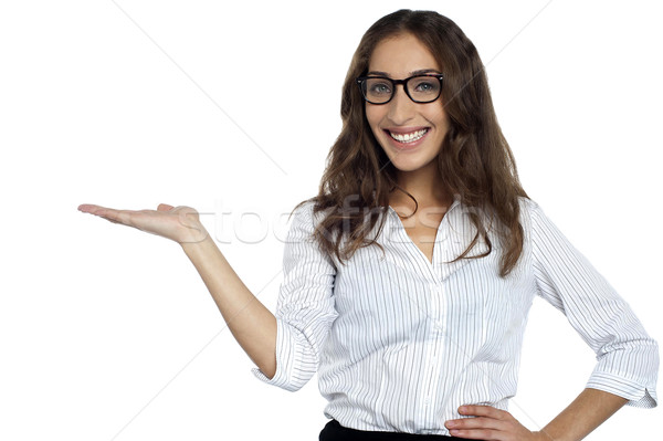 Joyous woman in spectacles posing with open palm Stock photo © stockyimages