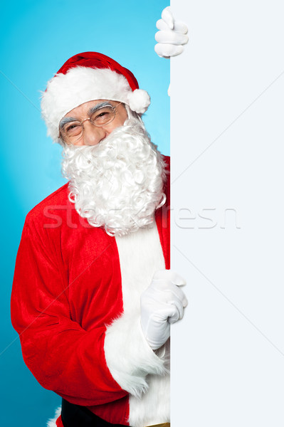 Santa posing beside long blank banner ad Stock photo © stockyimages