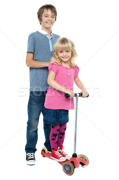 Brother holding her sister as she rides her toy scooter Stock photo © stockyimages