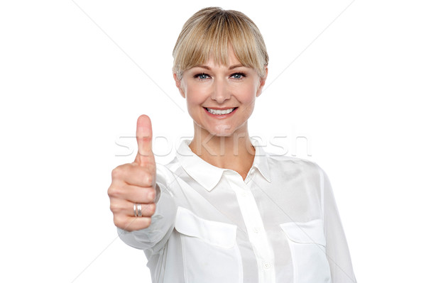 Blonde woman in formal attire showing thumbs up gesture Stock photo © stockyimages