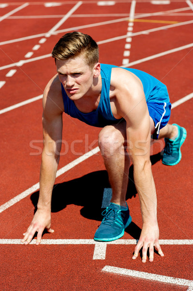 Young male sprinter in starting blocks Stock photo © stockyimages